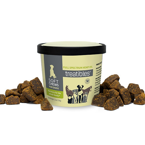 Container of CBD dog treats surrounded by small brown dog treats