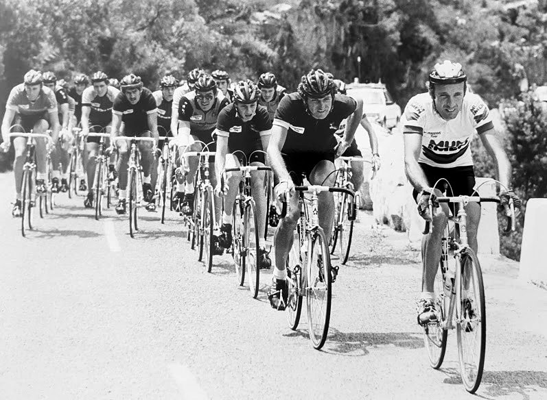 A black and white photo of John Heard cycling in South Africa