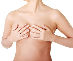 topless woman covering her breasts with her hands - torso view