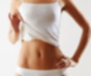 a woman wearing white panties and camisole, pulling top up to show flat stomach