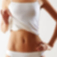 a woman in white undergarment, pulling up top to show flat tummy