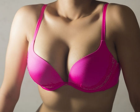 a woman's upper body wearing a hot pink bra