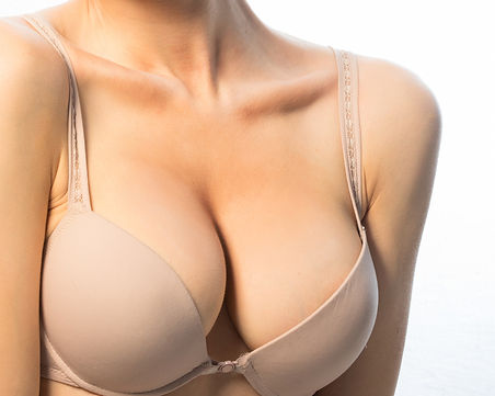 a woman with large breasts' upper body wearing a beige bra