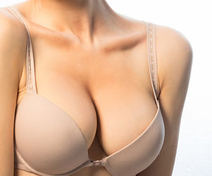 a woman wearing a beige bra - upper body without face showing