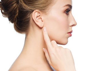 a woman's showing the side of her face and neck, pointing to ear