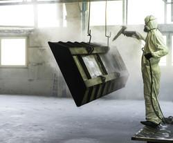 Worker Sandblasting Metal Piece