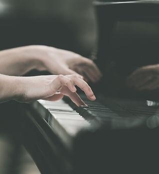 Manos chica tocando el piano