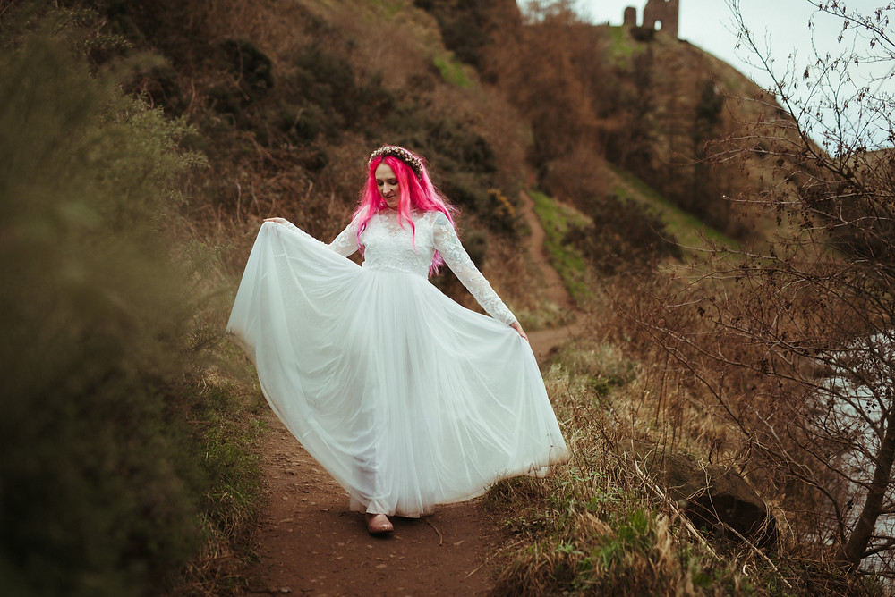 A bride with a flowers crown and pink hair in Edinburgh at Holyrood Park. She is wearing a white flowing wedding dress with lace sleeves is from ASOS. Her wedding flower crown is from Snapdragon Edinburgh. The bohemian bride is dancing in Holyrood Park. In the background you can see a ruin and a path leading up to it.