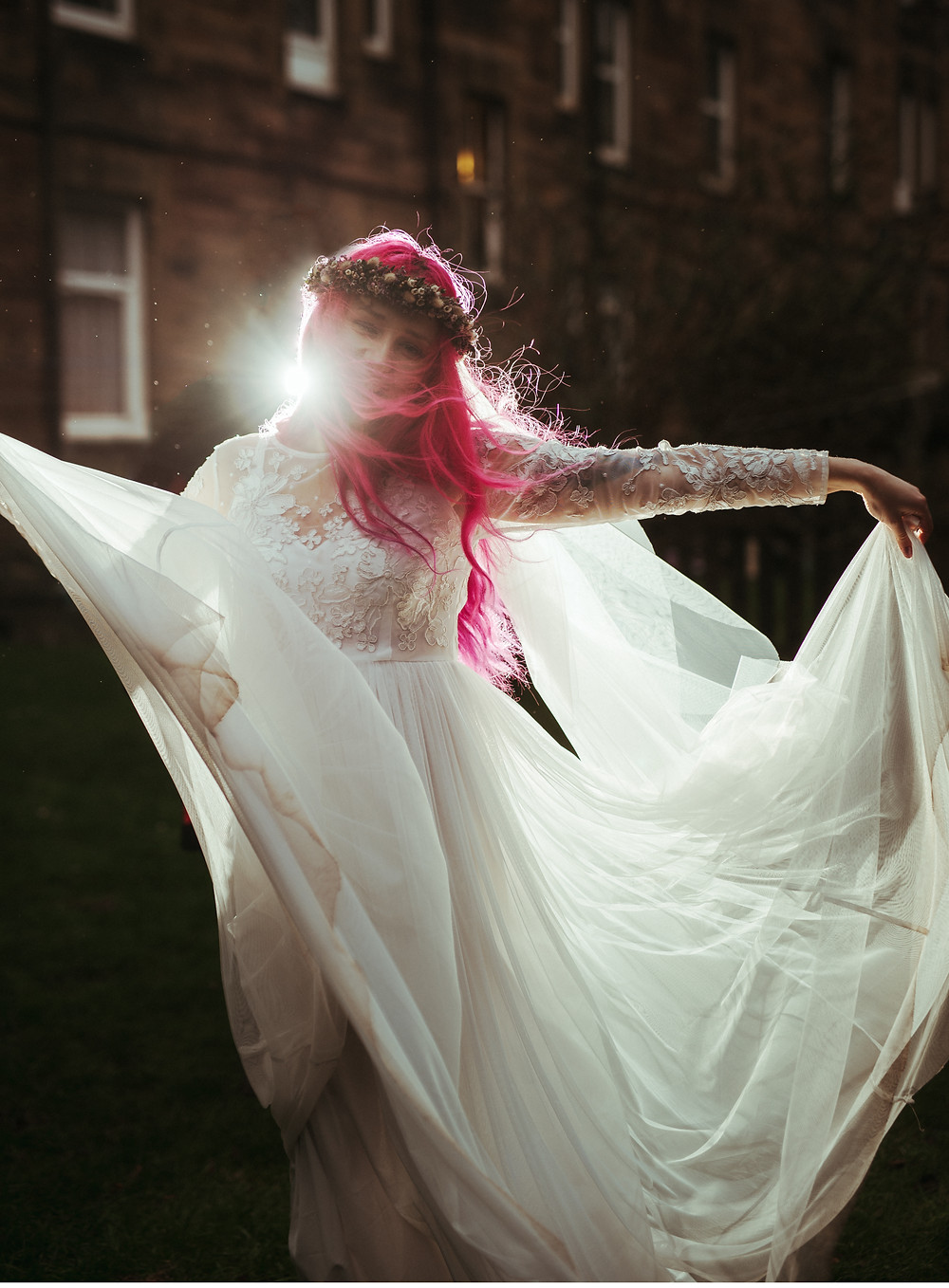 An alternative bride with a flowers crown and pink hair in Edinburgh at Holyrood Park. She is wearing a white flowing wedding dress with lace sleeves is from ASOS. Her wedding flower crown is from Snapdragon Edinburgh. The boho bride is dancing with her flow wedding dress during dusk.