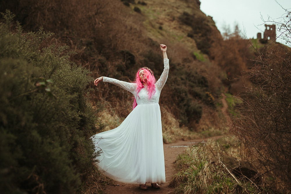 A bride with a flowers crown and pink hair in Edinburgh at Holyrood Park. She is wearing a white flow wedding dress from ASOS. Her flower crown is from Snapdragon Edinburgh. The bohemian bride is dancing through Holyrood Park. In the background you can see a ruin and a path leading up to it.