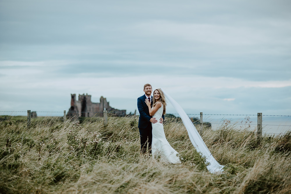 A bride and groom smiling in fron of Tantallon Castle near Edinburgh. They are freshly married. They got eloped in the countryside near Seacliff Beach with a view to Tantallon Castle. The bride is wearing a long veil which is flowing in the wind and a white simply beautiful wedding dress.