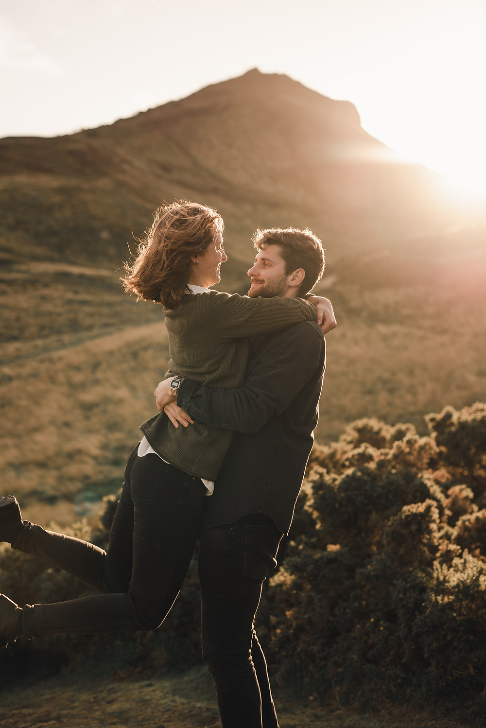 A couple who is in love hiked Arthurs seat to watch the sunset. On the way the enjoy the warmth of the sun, sitting down on the rocks in Holyrood Park and playfully dance in the grass on the hill, overlooking Edinburgh.