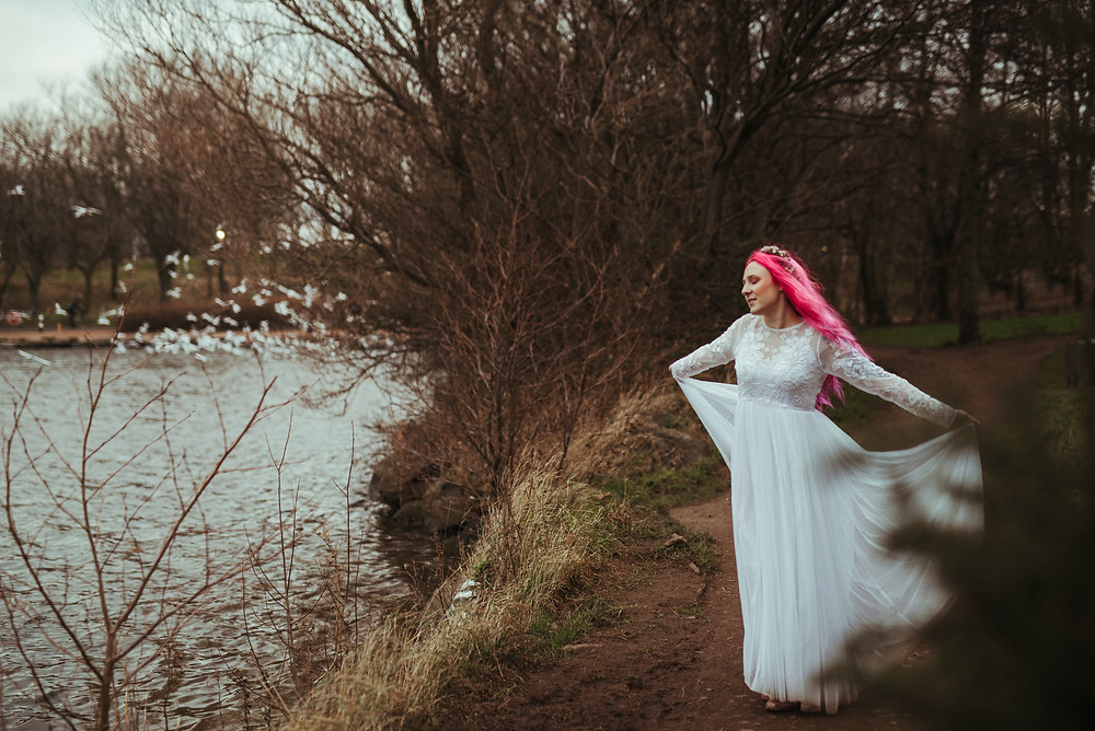 A bohemian bride with a flowers crown and pink hair in Edinburgh at Holyrood Park. She is wearing a white flowing wedding dress with lace sleeves is from ASOS. Her wedding flower crown is from Snapdragon Edinburgh. The bohemian bride is dancing near a loch in Holyrood Park in Edinburgh and the seagulls are flying by.