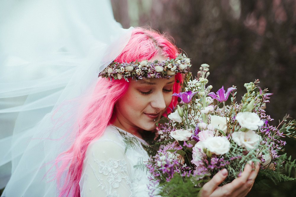 An alternative bride with a flowers crown and pink hair in Edinburgh at Holyrood Park. She is wearing a white flowing wedding dress with lace sleeves is from ASOS. Her wedding flower crown and the wedding bouquet is from Snapdragon Edinburgh.