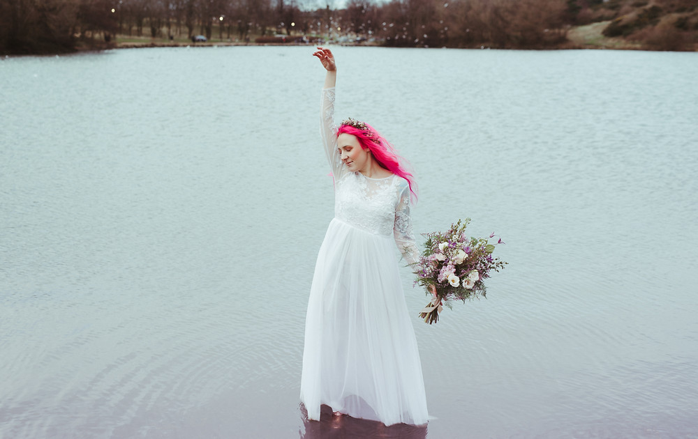 An alternative bride with a flowers crown and pink hair in Edinburgh at Holyrood Park. She is wearing a white flowing wedding dress with lace sleeves is from ASOS. Her wedding flower crown is from Snapdragon Edinburgh. The boho bride is dancing with her flowing wedding dress in a loch at Holyrood Park