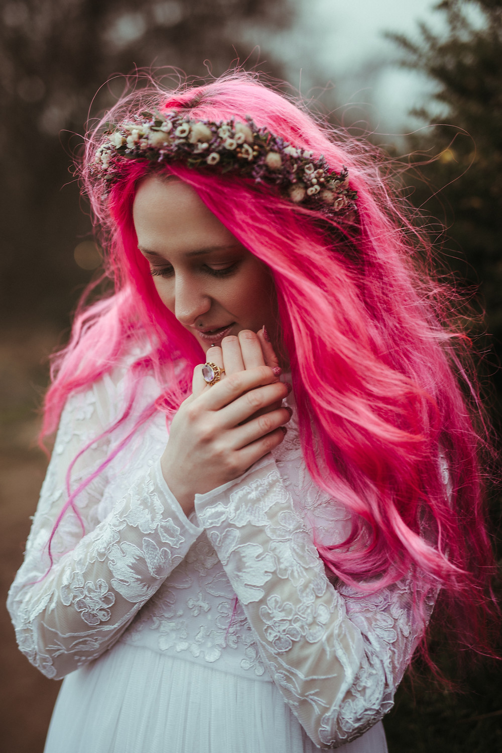 An alternative bride with a flowers crown and pink hair in Edinburgh at Holyrood Park. She is wearing a white flowing wedding dress with lace sleeves is from ASOS. Her wedding flower crown is from Snapdragon Edinburgh.