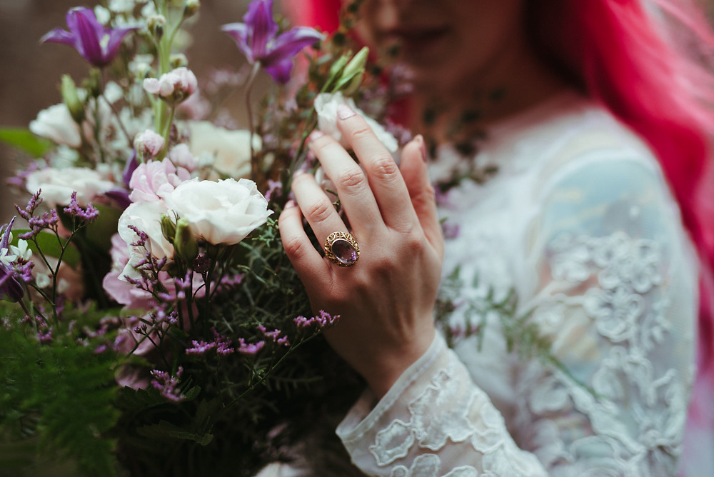 A bride with a flowers crown and pink hair in Edinburgh at Holyrood Park. She is wearing a white flowing wedding dress with lace sleeves is from ASOS. Her wedding bouquet is from Snapdragon Edinburgh. The bohemian bride is standing in Holyrood Park.
