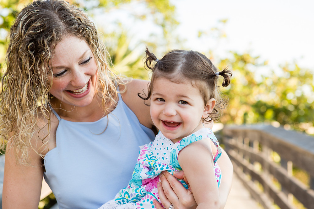 curly haired mom holding toddler girl with pigtails