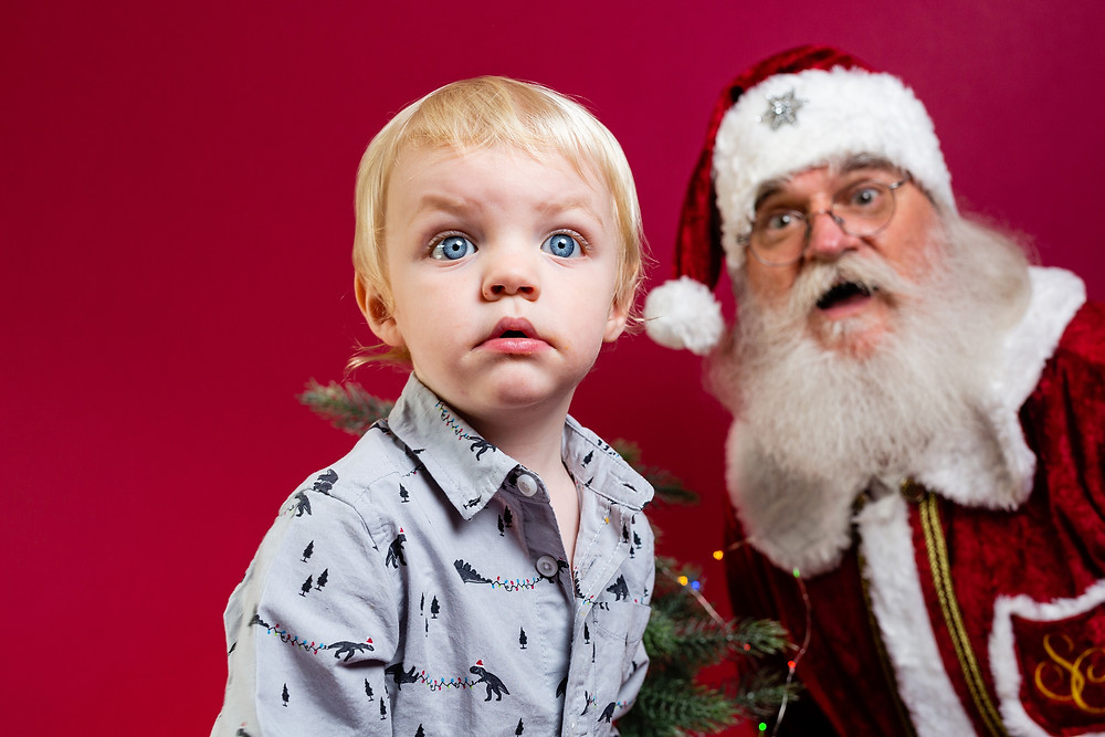 Santa and little boy looking surprised behind camera, red background