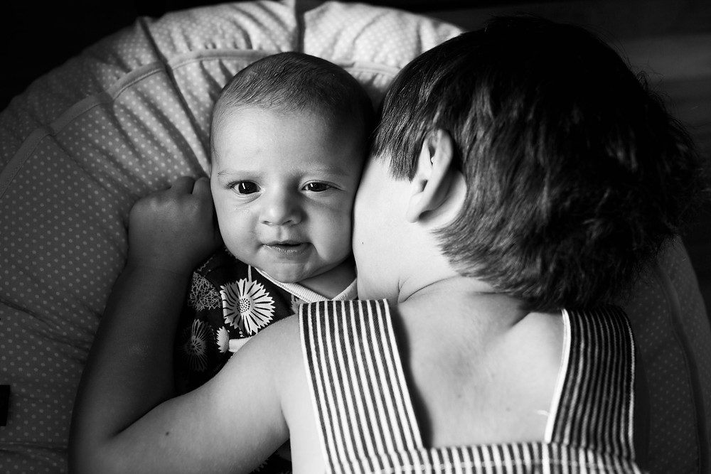 big brother kissing baby sister, black and white