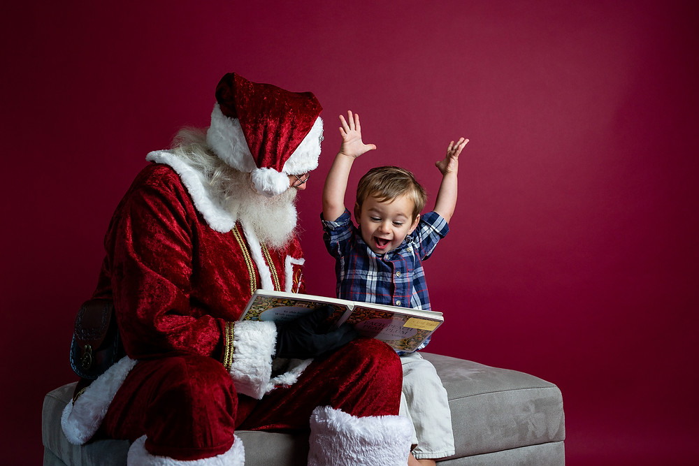 Santa reading book to little boy who has his arms raised