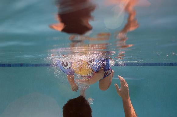 boy_and_dad_swimming_in_pool_baby_float_