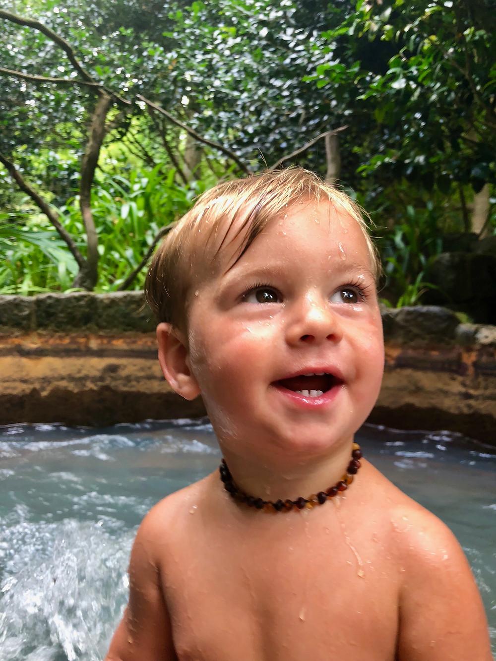 smiling boy wearing amber teething necklace