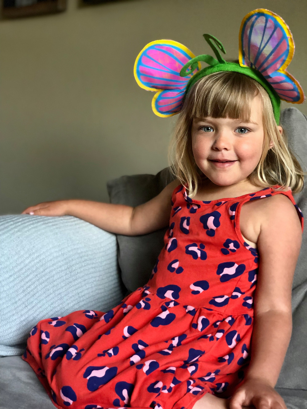 little girl wearing red dress and butterfly headband