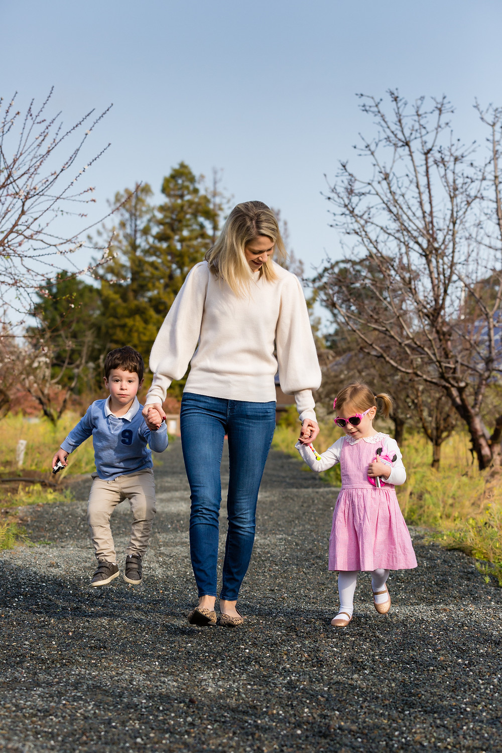 blonde mother walking with young son and daughter in San Jose, CA