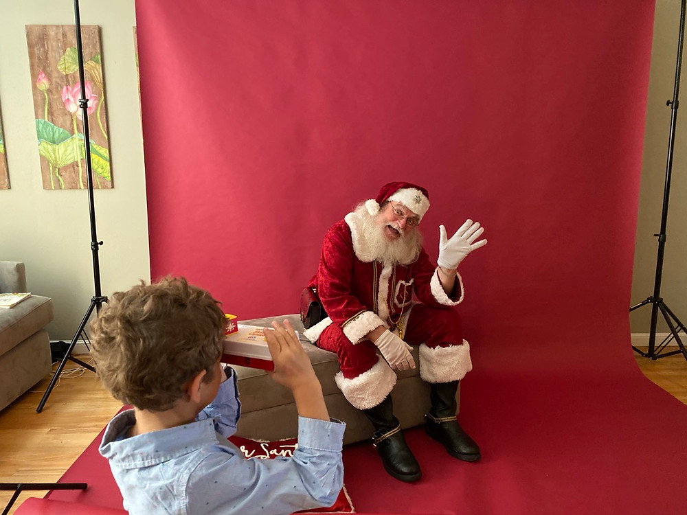 Santa waving to boy, red background, holiday minis background