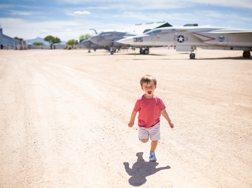 little boy running, with fighter jet in background