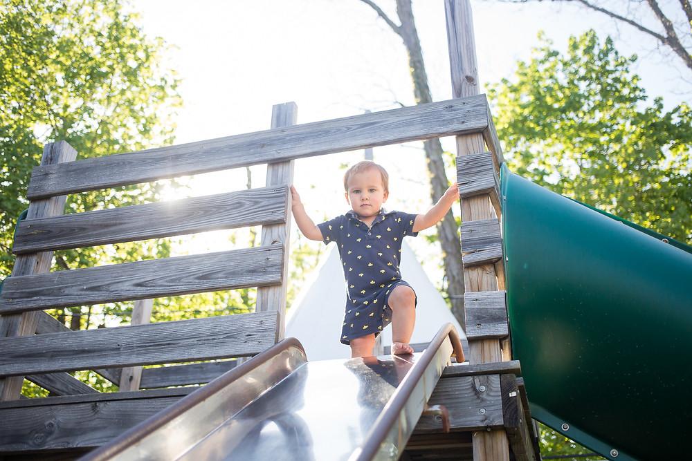 little boy at top of slide