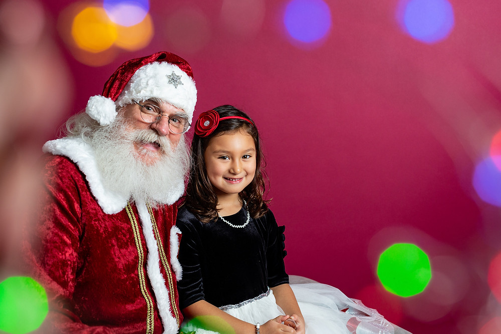Santa and little girl looking at the camera and smiling, colorful Christmas light bokeh