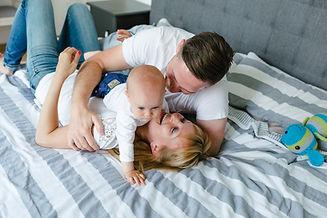 Familie, Eltern mit Baby auf dem Bett, Kuscheln, Familienfotografie, Familienshooting Frankfurt
