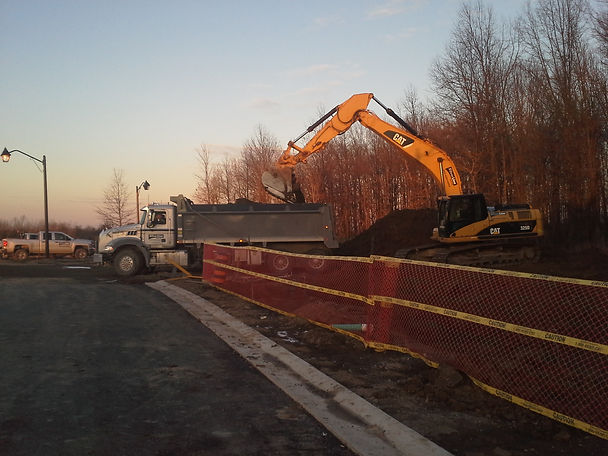 Dump truck and machine working on excavation