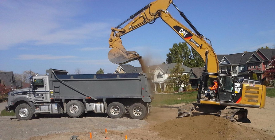 dump truck and machine working on trucking project