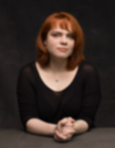 Author Alison Downs sits facing the camera with her hands clasped in front of her.