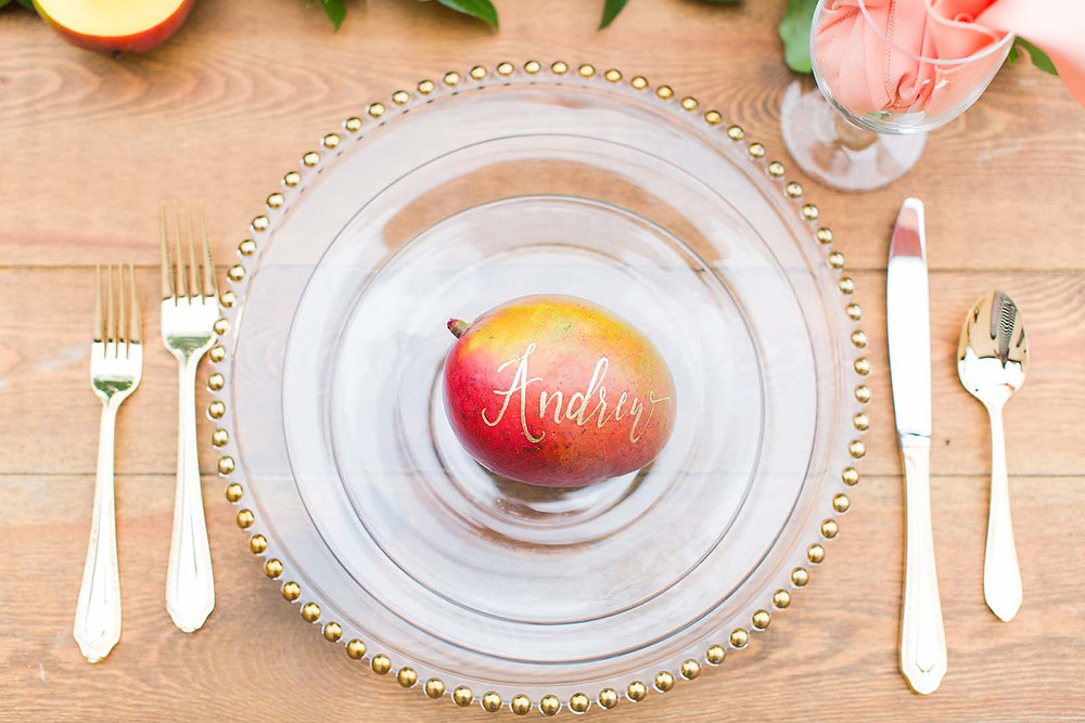 Hand-lettered mango on top of clear table setting with gold flatware.