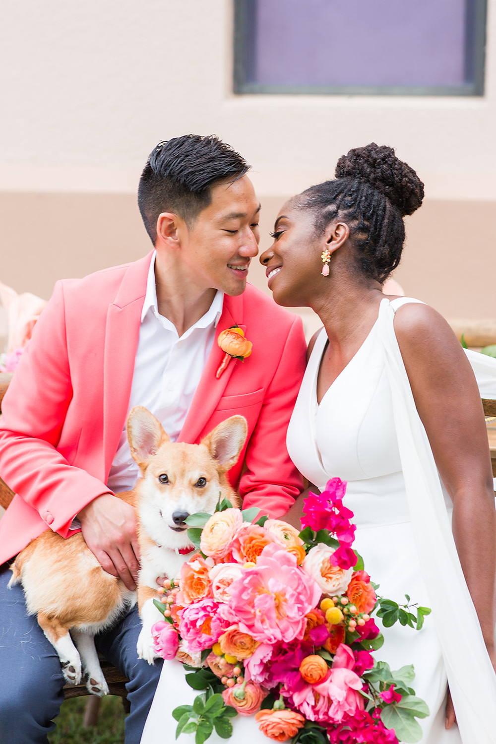 Bride and groom smiling at each other with their corgi.