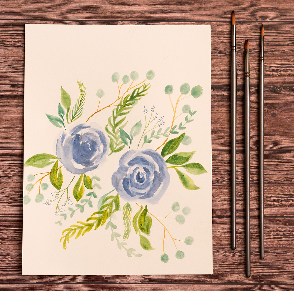 Watercolor florals on white paper with a wooden background.
