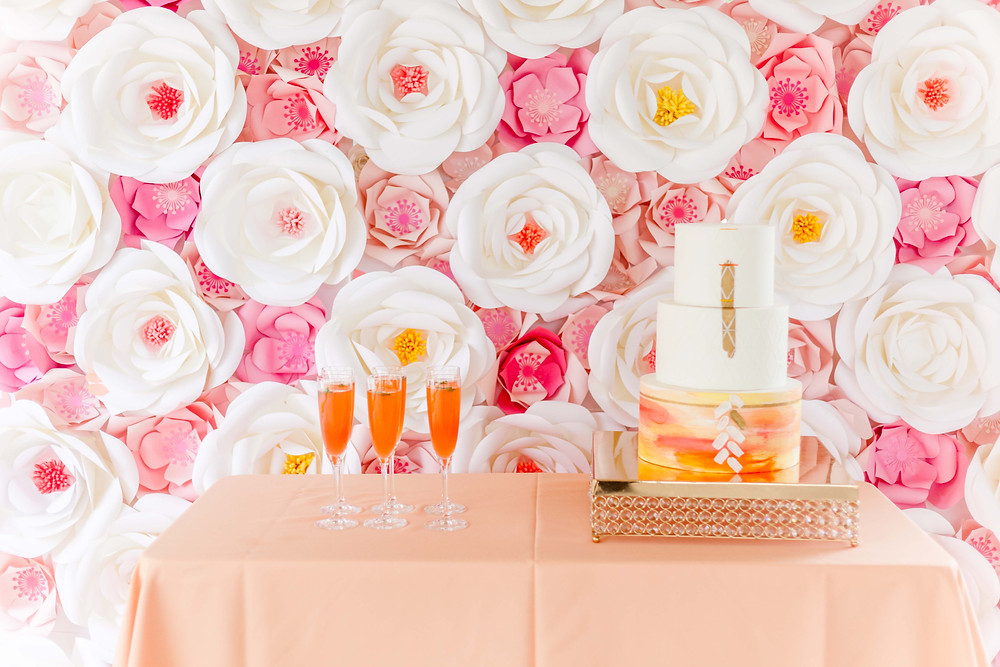 Pink and white paper flower wall behind an orange and white cake and champagne flutes.
