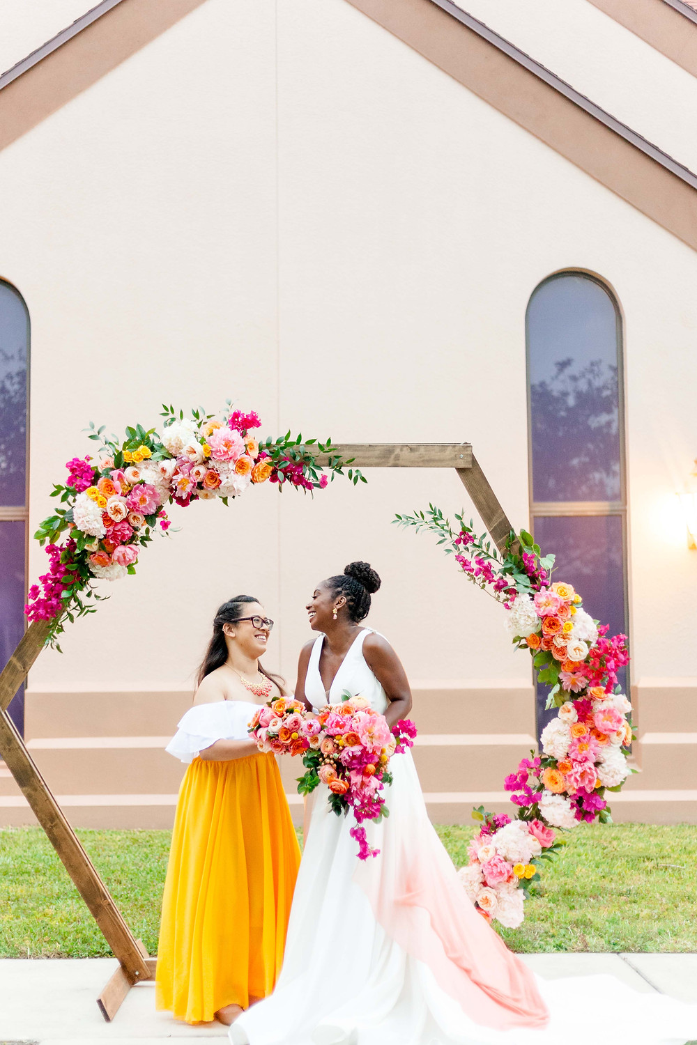 Bride and bridesmaid in front of hexagon arch.