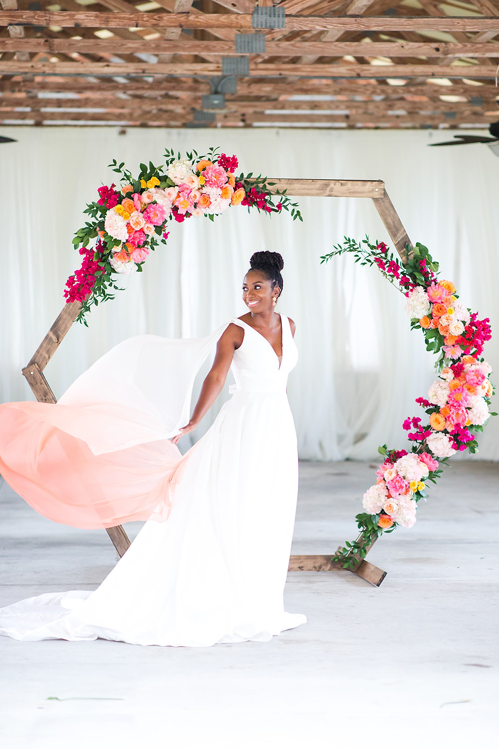Bride in flowing cape in front of hexagon arch with bright pink florals.