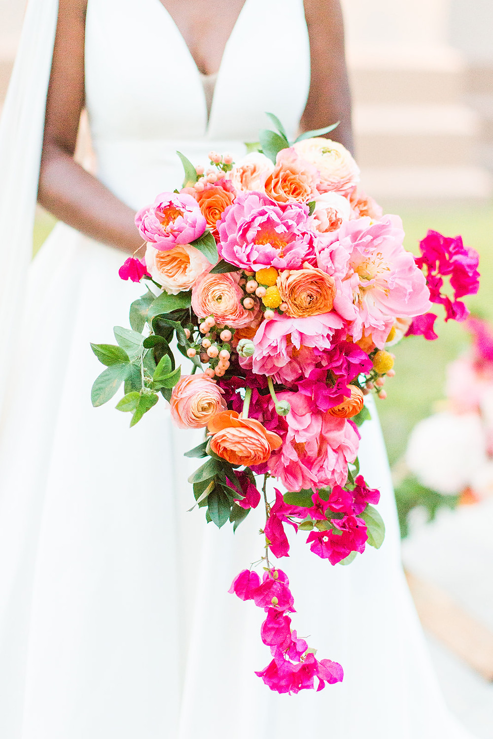 Bride holding waterfall bouquet of bright pink and orange flowers
