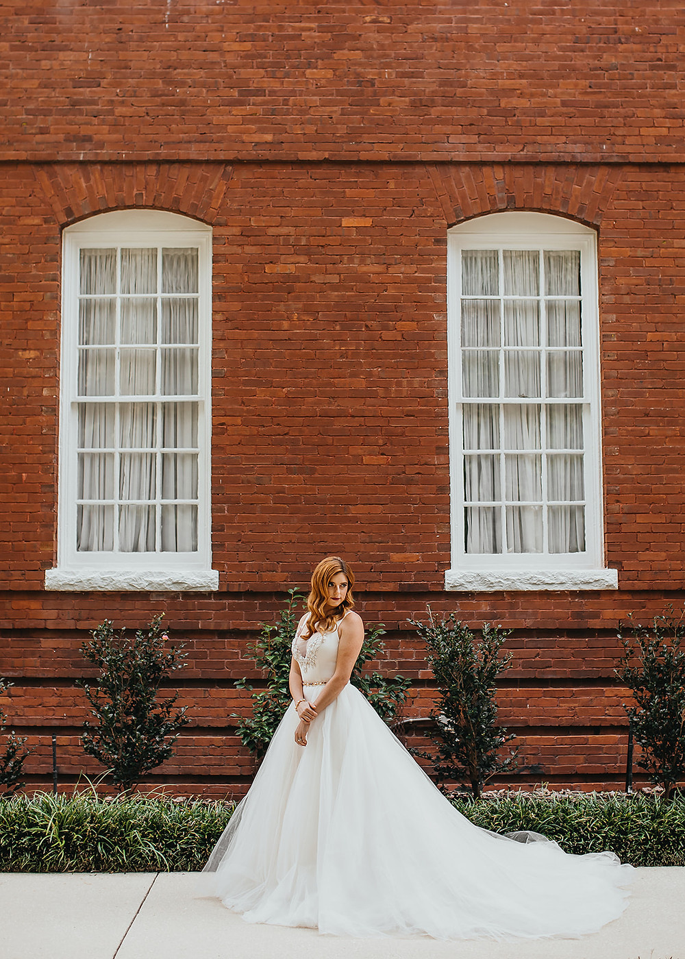 Woman in wedding dress in front of red brick building
