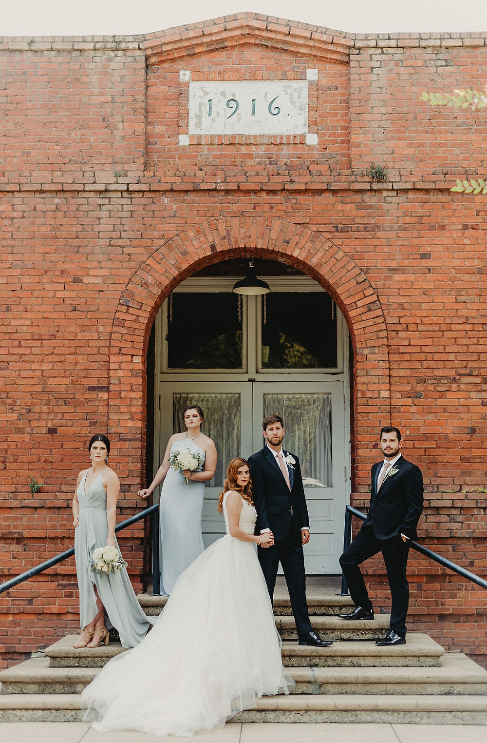 Bride, groom and wedding party in front of red brick building