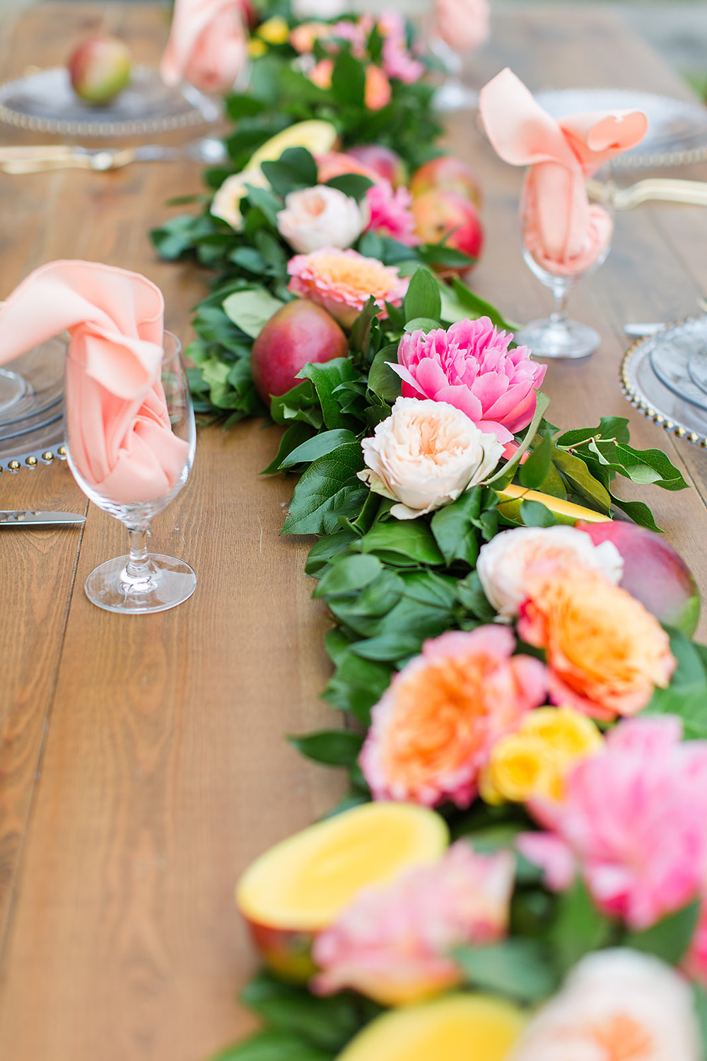 Bright floral garland down the middle of a table with drink and serve ware.