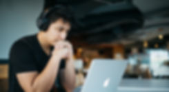 man wearing headphones while sitting on chair in front of MacBook_edited.jpg
