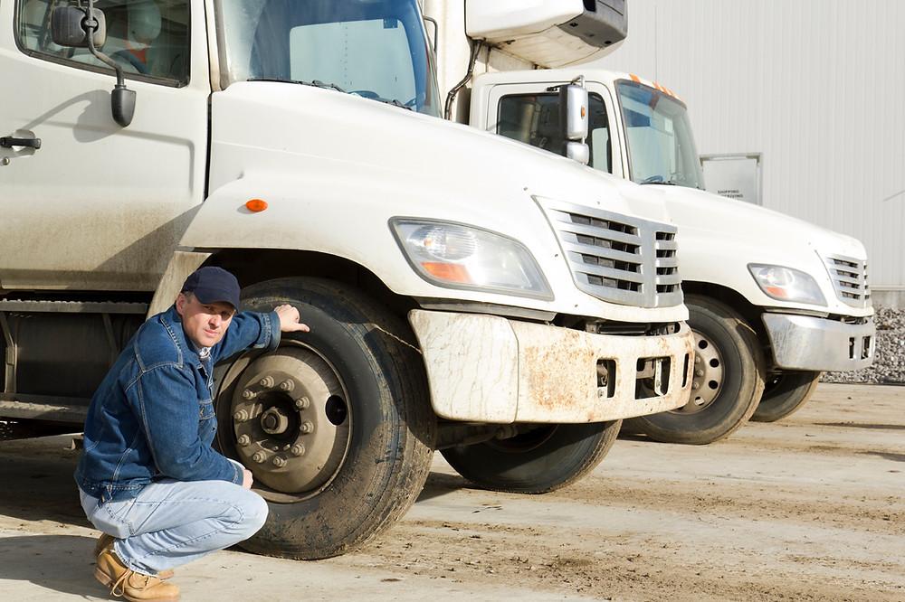 Trucker Checking Tires for Better CSA Scores
