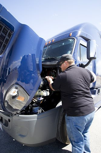 Trucker Performing a Pre-Trip Truck Inspection